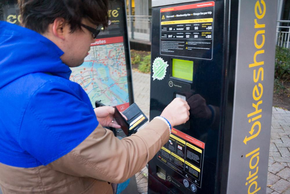 自動支払機にクレジットカードを挿入する友人